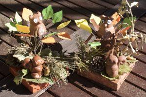 écureuil et hibou en plâtre dans un décor d'automne avec des feuilles et une pomme de pin
